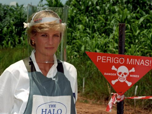 Diana, Princess of Wales, wears a protective mask and jacket as she stands next to a warning sign on the edge of a minefield in Angola (John Stillwell/PA)