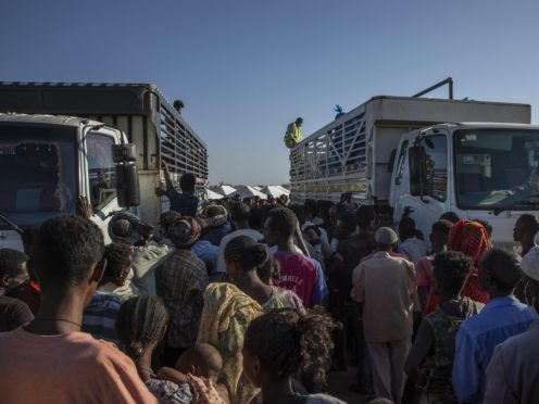 Refugees who fled the conflict in Ethiopia's Tigray region wait to receive aid at Umm Rakouba refugee camp in Qadarif, eastern Sudan (Nariman El-Mofty/AP)