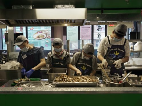 Staff work at Dignity Kitchen in Hong Kong (Vincent Yu/AP)