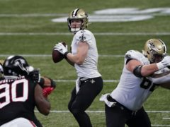 Taysom Hill, centre, led the Saints to victory and a play-off berth (John Bazemore/AP)