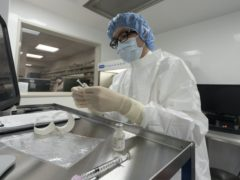 A pharmacist labels syringes in a clean room where doses of Covid-19 vaccines will be handled at Mount Sinai Queens hospital in New York (Mark Lennihan/AP)