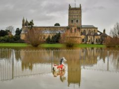 Children's playground equipment pokes out from floodwater surrounding Tewkesbury Abbey (Ben Birchall/PA)