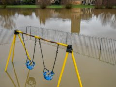 Children's playground equipment pokes out from floodwater surrounding Tewkesbury Abbey (PA)