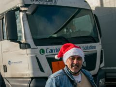 A man wearing a Santa hat walks past a freight lorry queuing to enter the Port of Dover in Kent (Aaron Chown/PA)