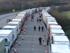 Drivers walk along the road next to freight lorries lined up on the M20 near Ashford, Kent (PA)