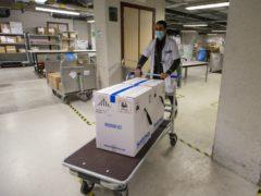 Medical staff receive part of a Pfizer/BioNTech Covid-19 vaccine shipment at the UZ Leuven hospital in Leuven, Belgium (Nicolas Maeterlinck, Pool via AP)