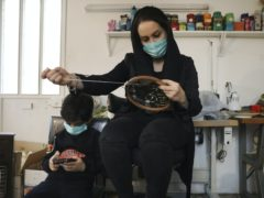 Elaheh Rahimi embroiders at a workshop of Bavar charity in Tehran, Iran (Vahid Salemi/AP)