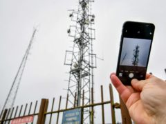 File photo dated 27/01/20 of a mobile phone next to telecom masts near Dundry, Somerset. The rollout of 5G will open the UK up to security risks such as espionage, sabotage and system failure affecting individuals, government and defence, MPs have warned.