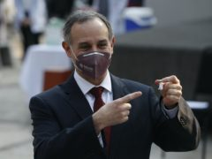 Mexico's coronavirus response leader Hugo Lopez-Gatell points to a vial of the Covid-19 vaccine (Eduardo Verdugo/AP)