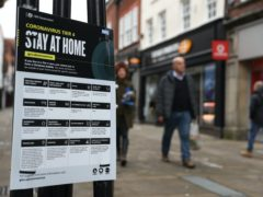 People make their way past a Government coronavirus Tier 4 sign on a high street (Andrew Matthews/PA)