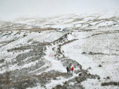 Walkers ascend the path to the top of Pen y Fan, South Wales' highest mountain, in snowy conditions (Ben Birchall/PA)