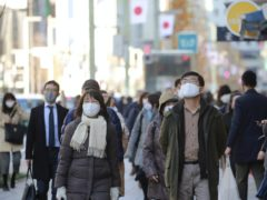 People wearing face masks to protect against the spread of the coronavirus walk at Ginza shopping street in Tokyo on Monday (Koji Sasahara/AP)