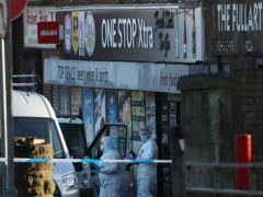 Police officers in forensic suits at the scene of an investigation outside the One Stop shop (Andrew Milligan/PA)