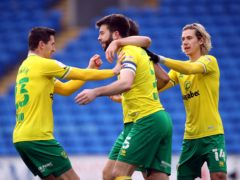 Grant Hanley (centre) celebrates the opening goal for Norwich at Cardiff (Nick Potts/PA)
