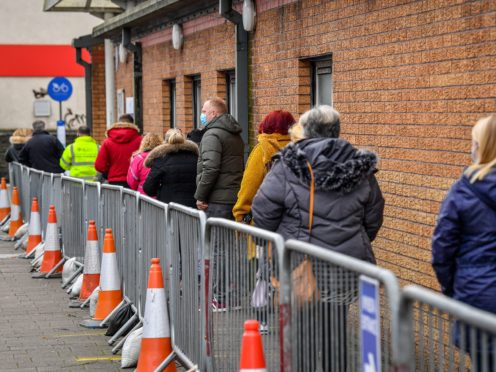 People queue for a vaccine in Wales (Ben Birchall/PA)