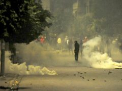 Demonstrators face police officers during clashes in Ettadhamen City near Tunis (Hassene Dridi/AP)