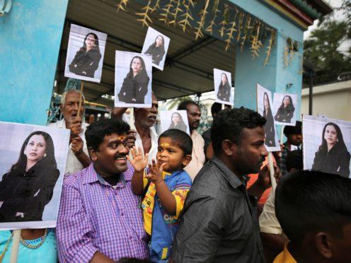A child reacts as villagers hold placards featuring Kamala Harris (Aijaz Rahi/AP)