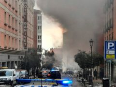 Smoke rises from a building and rubble scattered in Toledo Street following a explosion in Madrid (Europa Press via AP)