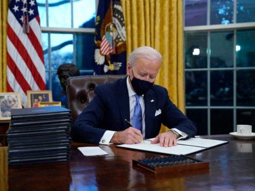 President Joe Biden signs his first executive order in the Oval Office (Evan Vucci/AP)
