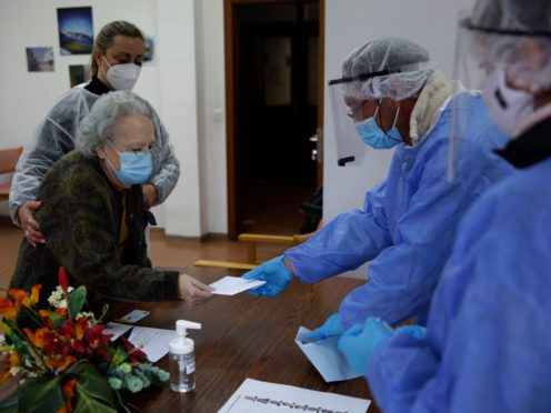 A woman hands her presidential election ballot to municipal workers in protective gear at the elderly care home where she resides in Portugal (Armando Franca/AP)