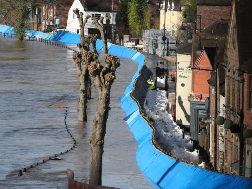 Sandbags are delivered alongside the flood defences at the Wharfage on the River Severn in Ironbridge, Shropshire (Nick Potts/PA)