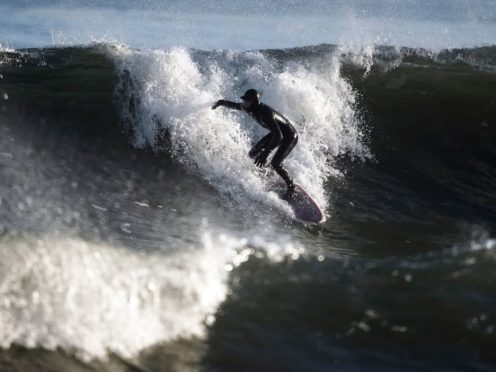 Surfers in the sea off the coast at Blyth beach, in Northumberland (Owen Humphreys/PA)