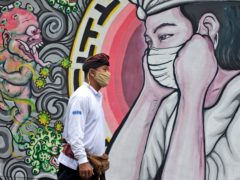 A man walks past a coronavirus-themed mural in Bali, Indonesia (Firdia Lisnawati/AP)