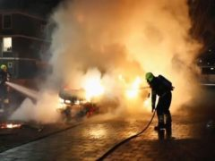 In this grab taken from video on Monday, Jan, 25, 2021, firefighters extinguish a vehicle set on fire by rioters, in Haarlem, Netherlands. Groups of youths have confronted police in several Dutch cities defying the country's coronavirus curfew and throwing fireworks. Police in the port city of Rotterdam used a water cannon and tear gas in an attempt to disperse a crowd of rioters Monday night. (Mizzle Media via AP)