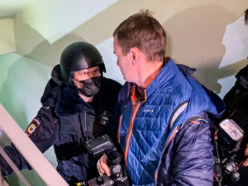 A police officer pushes photographers from a door of the apartment where Oleg Navalny was arrested (Mstyslav Chernov/AP)