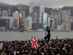Thousands of protesters carrying the British flag march near the Hong Kong harbour in July 2019 (Kin Cheung/AP)