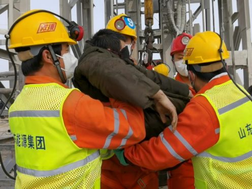 Rescuers carry a miner who was trapped in a gold mine in Qixia City in east China's Shandong Province (Xinhua News Agency/AP)