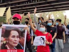 Protesters flash the three-fingered salute and hold images of deposed Myanmar leader Aung San Suu Kyi as they march in Yangon, Myanmar (Democratic Voice of Burma/AP)