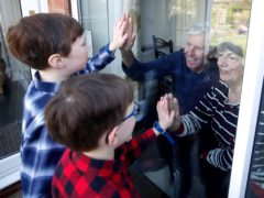 Ben and Isaac talk to their grandparents Sue and Alan through a window, as they self-isolate at their home in Knutsford, Cheshire (Martin Rickett/PA)