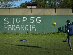 A man plays football in front of graffiti reading Stop 5G Paranoia on Wanstead Flats in east London (Victoria Jones/PA)
