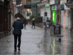 A man uses an umbrella as he walks up the empty High Street in Winchester, Hampshire (Andrew Matthews/PA)