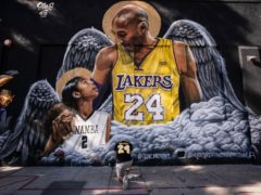 Adam Dergazarian, bottom centre, pays his respect for Kobe Bryant and his daughter, Gianna, in front of a mural painted by artist Louie Sloe Palsino (Jae C. Hong/AP)