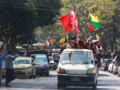 Buddhist religious and military flags are waved by supporters including Buddhist monks onboard a vehicle in Rangoon (Thein Zaw/AP)