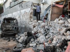 A hotel security guard stands by wreckage in the aftermath of an attack on the Afrik hotel in Mogadishu, Somalia (Farah Abdi Warsameh/AP)