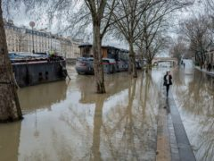 A girl walks ground between floodwaters on the banks of the river Seine in Paris (Rafael Yaghobzadeh/AP)