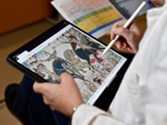 A technician working on a tablet on the digital version of the tapestry in Bayeux (Ville de Bayeux via AP)