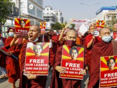 Buddhist monks display pictures of deposed leader Aung San Suu Kyi during a street march against the military coup in Mandalay, Myanmar on Friday, Feb. 12, 2021. Myanmar's coup leader used the country's Union Day holiday on Friday to call on people to work with the military if they want democracy, a request likely to be met with derision by protesters who are pushing for the release from detention of their country's elected leaders. (AP Photo)
