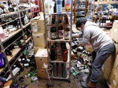 An off-licence's manager clears damaged bottles following an earthquake (Jun Hirata/Kyodo News via AP)