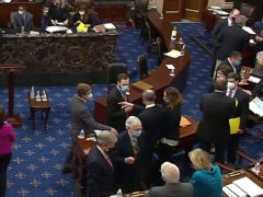 Senate minority Leader Mitch McConnell and other Republican legislators and staff talk on the floor of the US senate (AP)