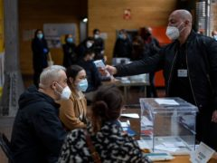 A man working at a polling station has his temperature taken (Emilio Morenatti/AP)