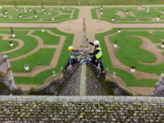 Stonemasons James Preston and John Fowler from SSH Conservation survey Kirby Hall in Corby, Northamptonshire (Joe Giddens/PA)