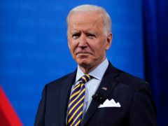 President Joe Biden stands on stage during a break in a televised town hall event (Evan Vucci/AP)