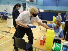 Prime minister Boris Johnson greets Senior Nurse Amanda Whent during a visit to a vaccination centre at Cwmbran Stadium in Cwmbran, south Wales (PA)