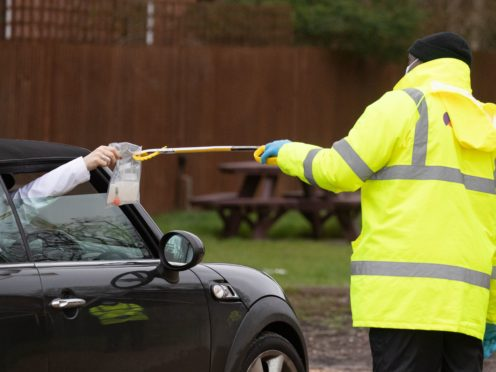 A coronavirus test is handed out of a car window (Andrew Matthews/PA)