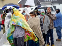 People wait in freezing rain in Houston to fill gas cylinders (David J Phillip/AP)