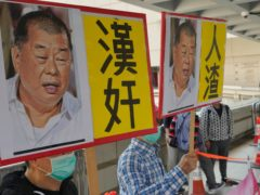 Pro-China supporters hold the pictures of prominent Hong Kong democracy advocate and newspaper founder Jimmy Lai with Chinese words 'Traitor of China' in Hong Kong on Thursday (Vincent Yu/AP)